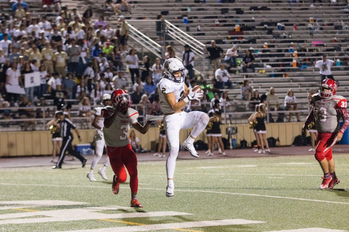 Football Player catching a touchdown on a Turf field