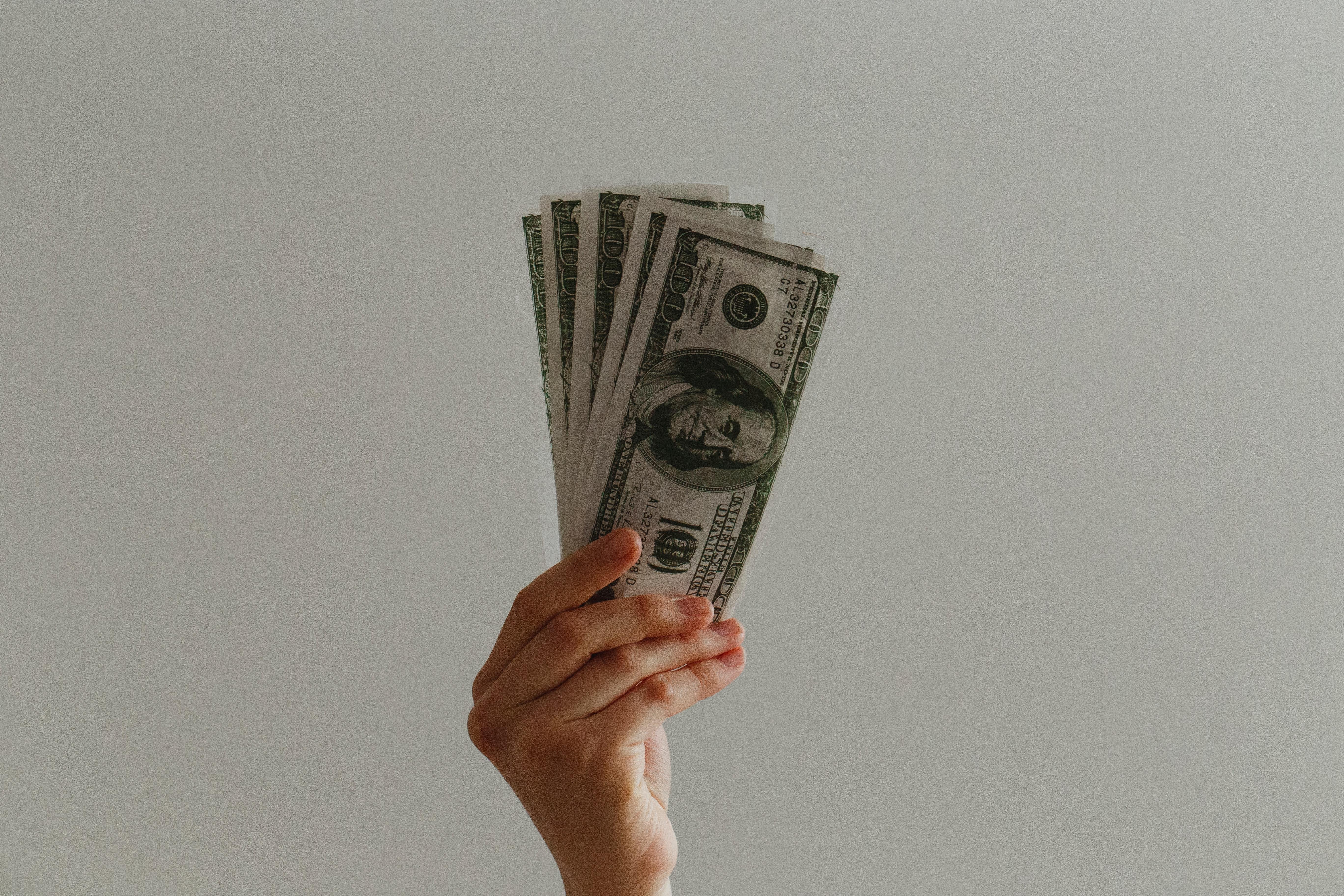 Hand holding one hundred dollar bills
