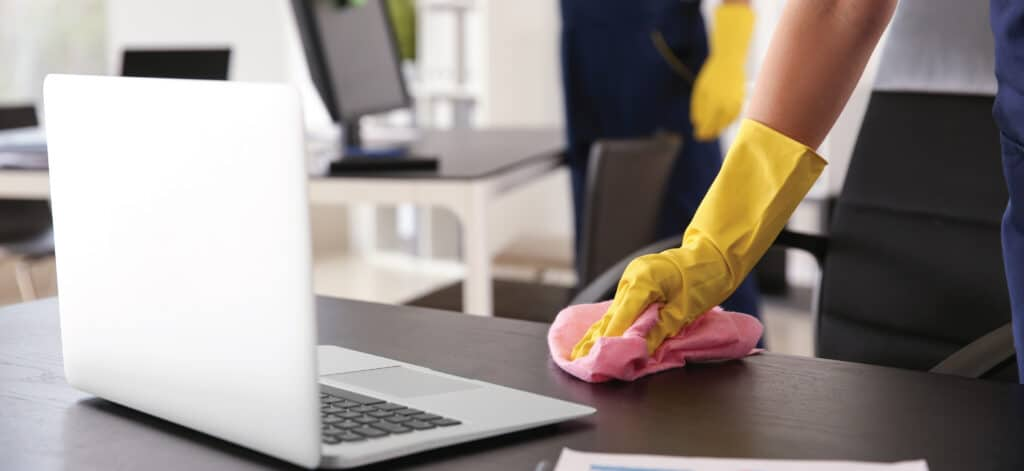Wiping off an office desk with a cleaning rag